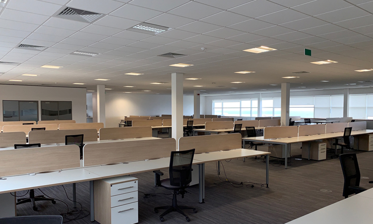 Large office room with empty desks and black chairs