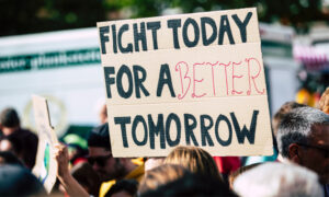 """Protestor sign saying """"fight today for a better tomorrow"""" at net zero rally"""